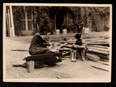 Two men sitting on planks