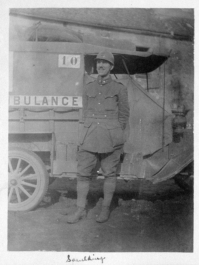 Goerge Spaulding standing by his ambulance